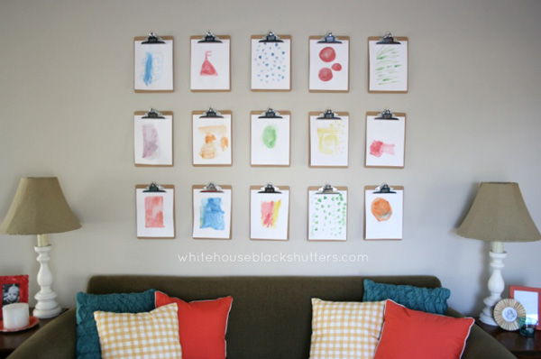 Wood clipboards holding art prints hanging on a wall above a sofa