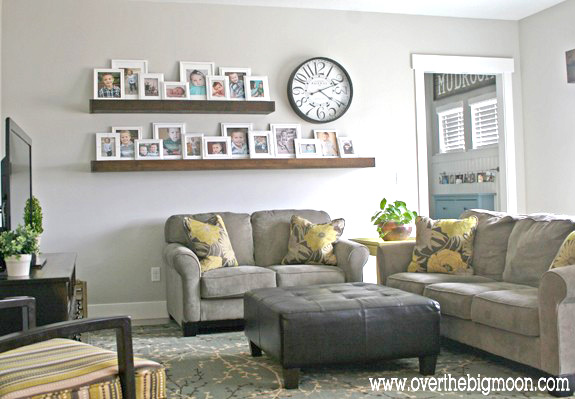 A living room filled with furniture and two long shelves on the wall filled with framed photos