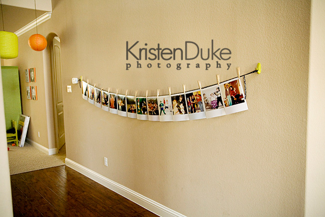 String hanging across a long wall with photos hanging from it
