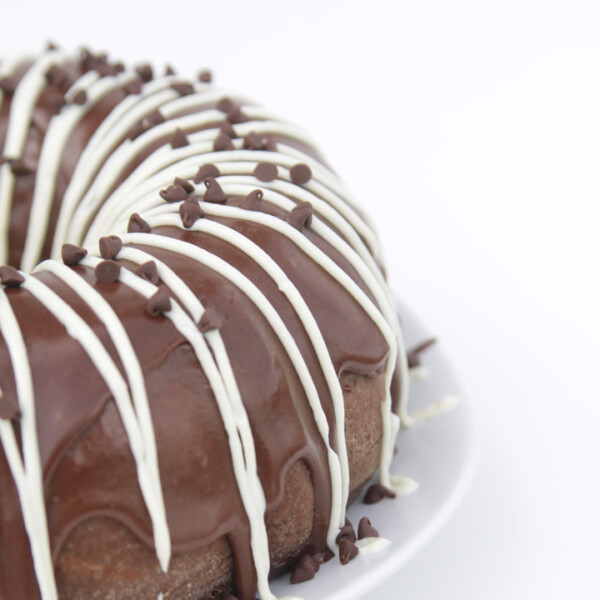A large chocolate cake on a plate with Cream cheese frosting