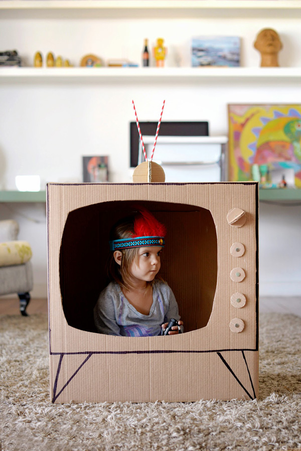 Little girl sitting inside a box made to look like a TV