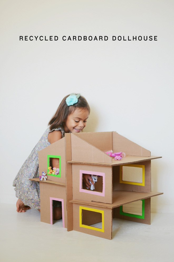 Girl playing with doll house made from cardboard