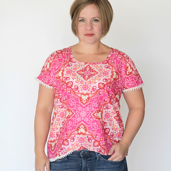 A woman wearing a pink blouse made from a sewing tutorial