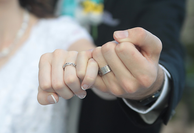 A close up of a bride and grooms hands and wedding rings