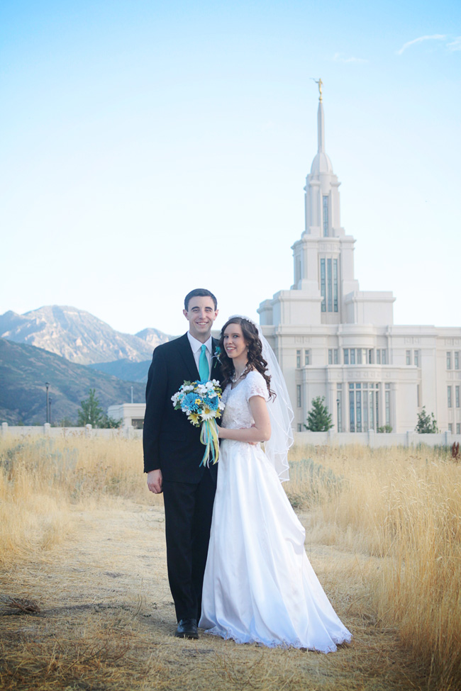 Bride and groom standing in a field in front of the temple they were married in