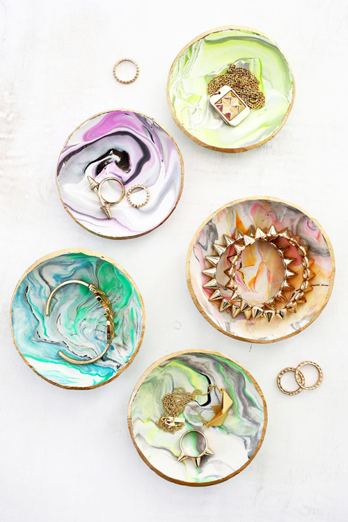 A close up of a pretty marbled ring dishes with jewelry in them
