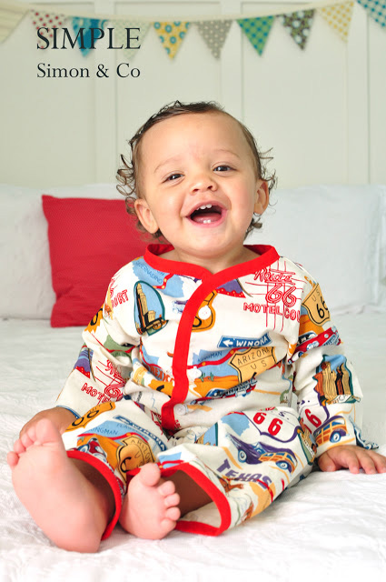 A small child sitting on a bed wearing pajamas