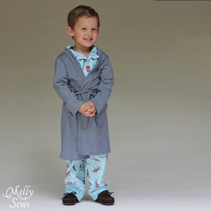 A little boy wearing blue pajamas and a robe
