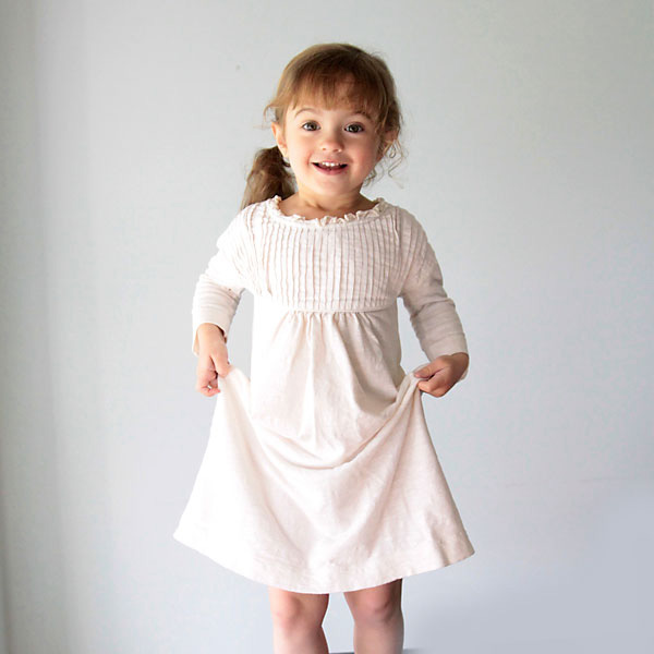 A little girl wearing a nightgown