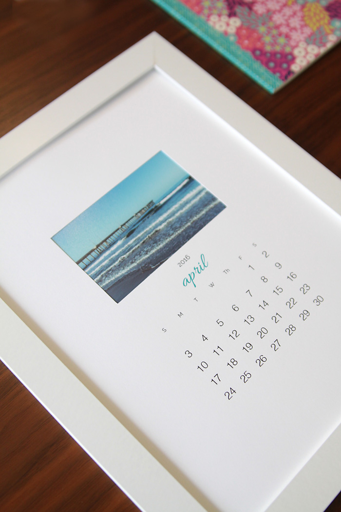 DIY photo calendar in a frame laying on a table