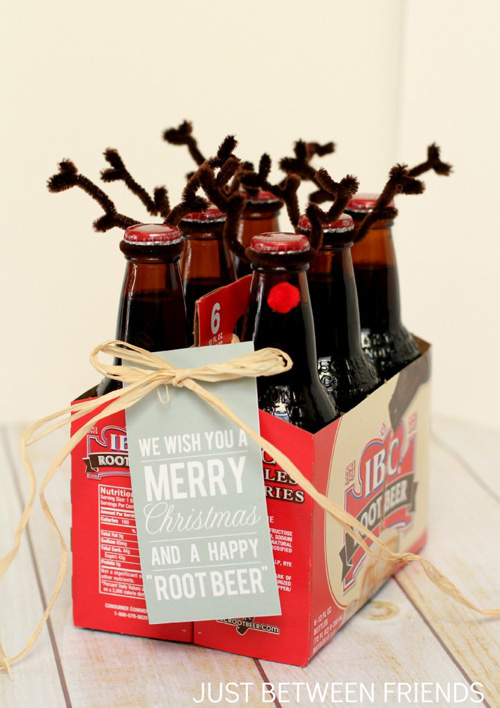Bottles of root beer decorated with pipe cleaners and red pom pom to look like reindeer with gift tag