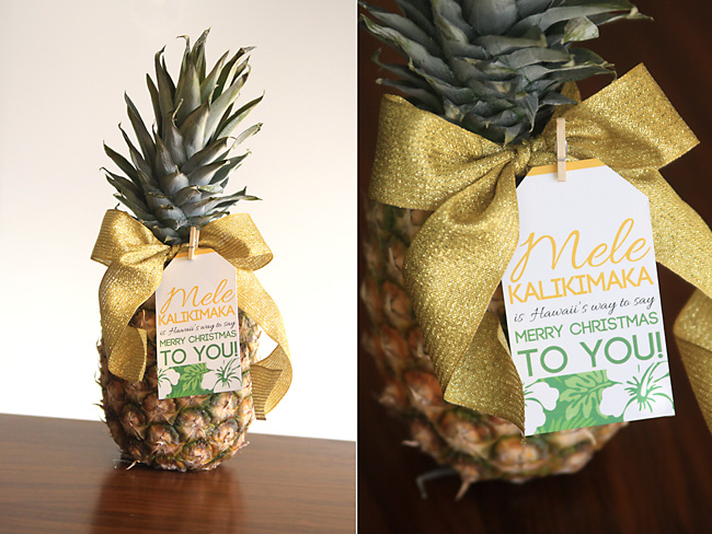 A pineapple on a wooden table with a gift tag for Christmas