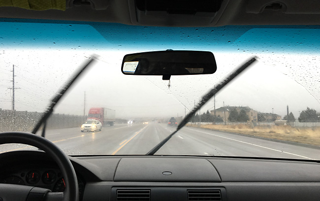A photo of the street taken out a car\'s from window with wipers going