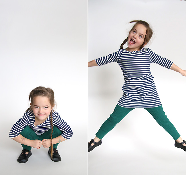 A little girl in sweater leggings jumping around