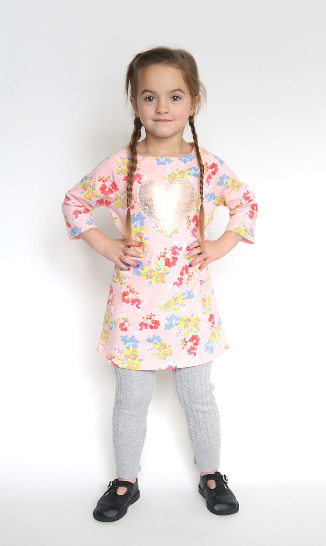 A little girl wearing a pink top and grey sweater leggings