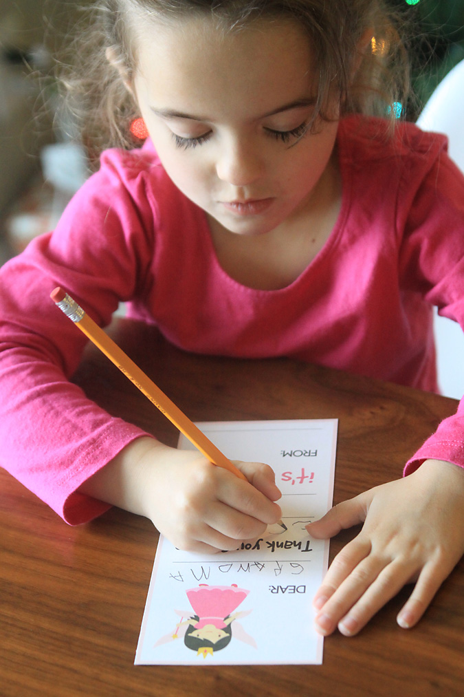 A little girl filling out a thank you card