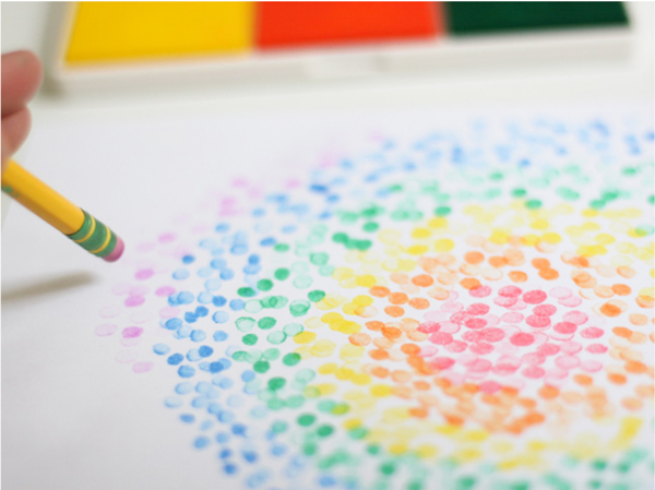 Pencil eraser being used to stamp colored circles on a piece of paper