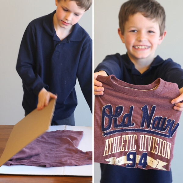 A boy using a large piece of cardboard to neatly fold a t-shirt