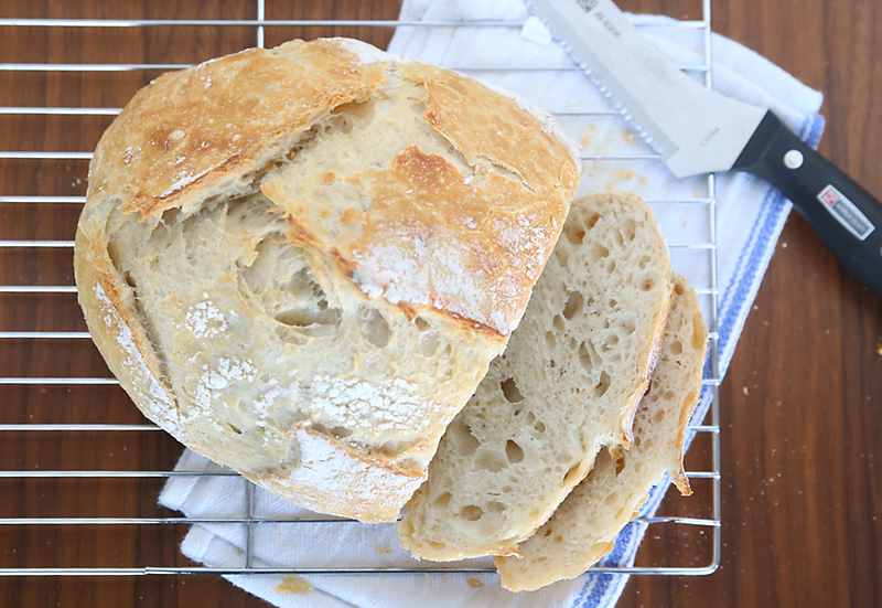 A rustic round loaf of artisan bread slice on a cooling rack