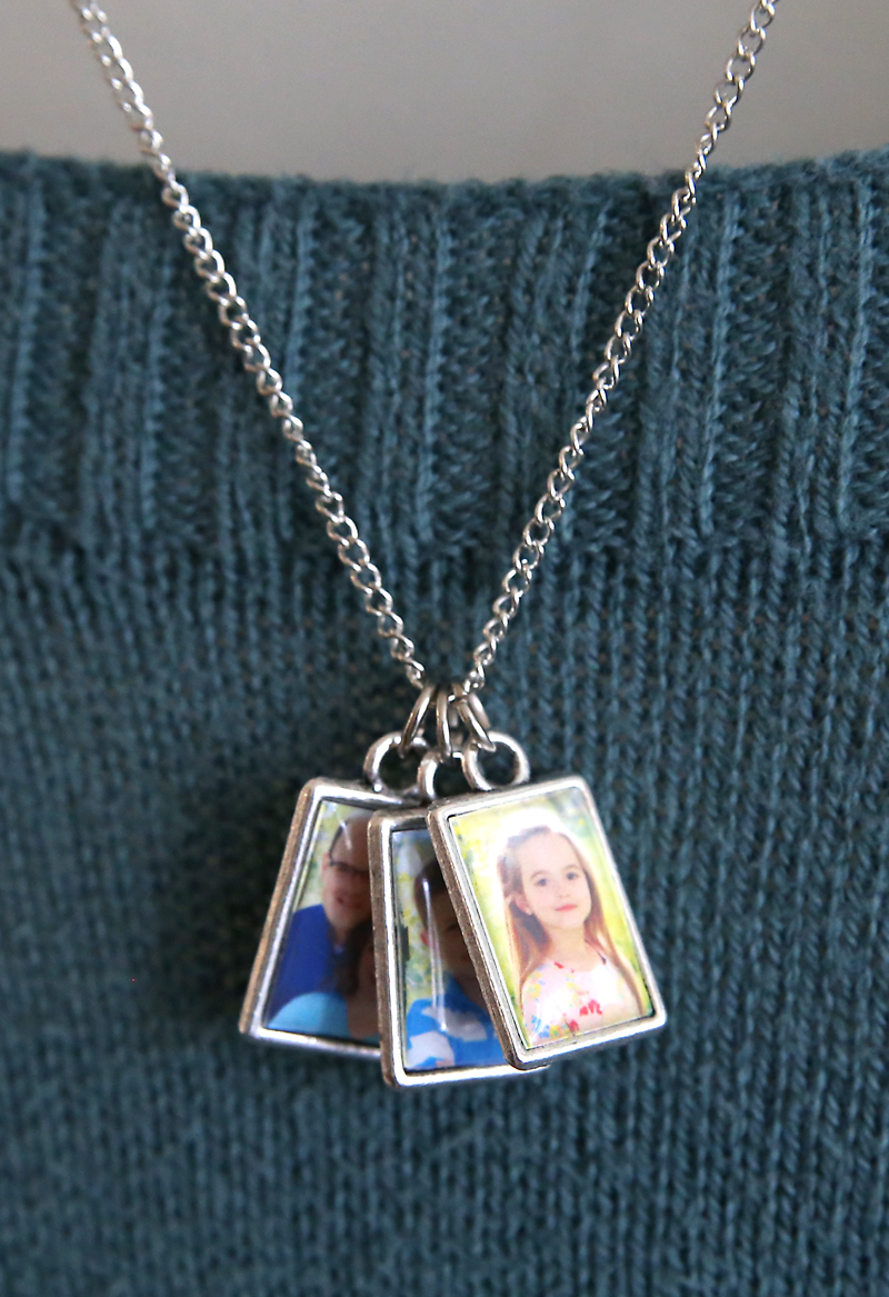A necklace with three photo pendants on it