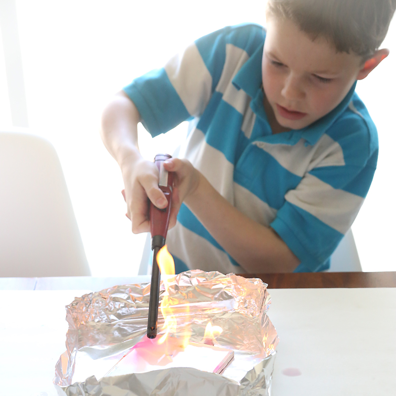 Boy using a lighter to set fired to the alcohol on the tile