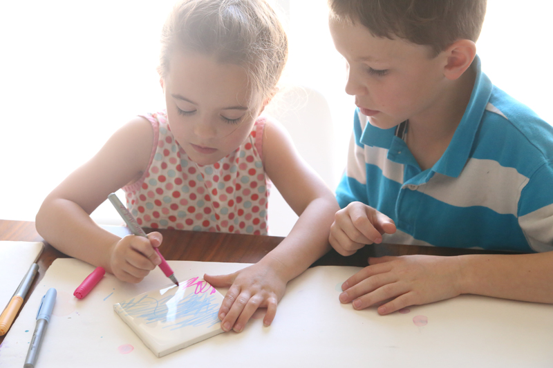 Two children coloring on a white tile to make fired tile art