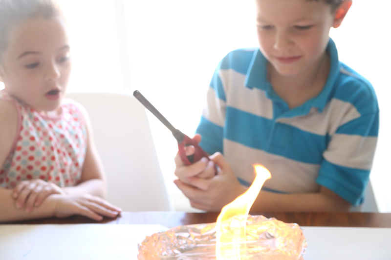 A boy watching the alcohol burn on a fired art tile
