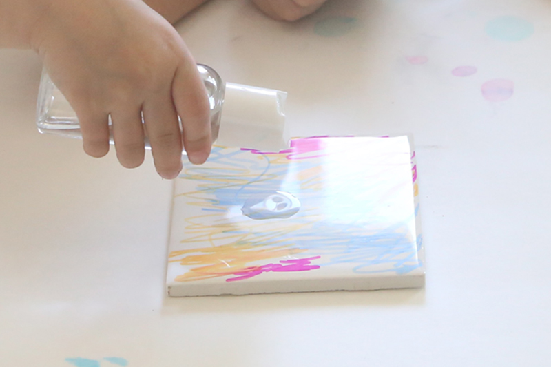 Hand pouring alcohol on colored tile