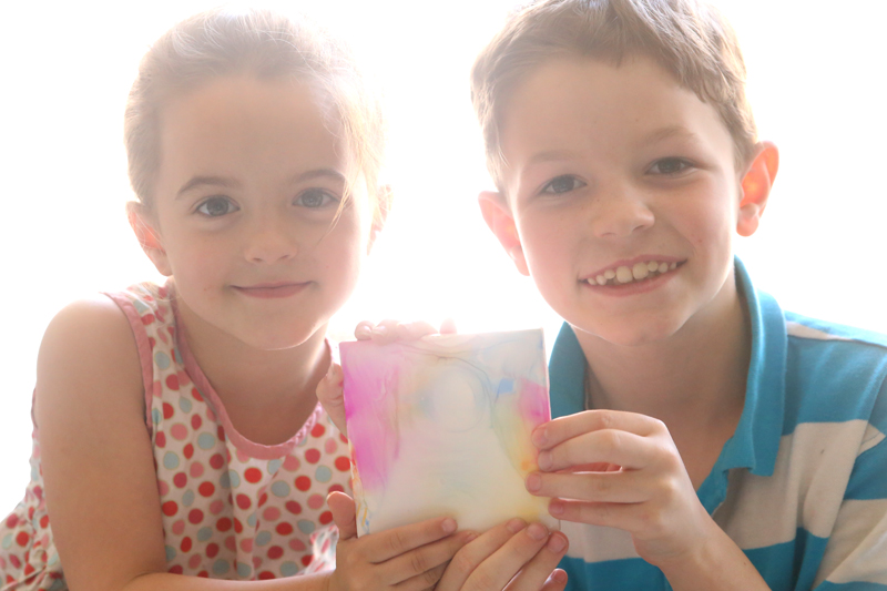 A boy and girl holding a the DIY tile art they made