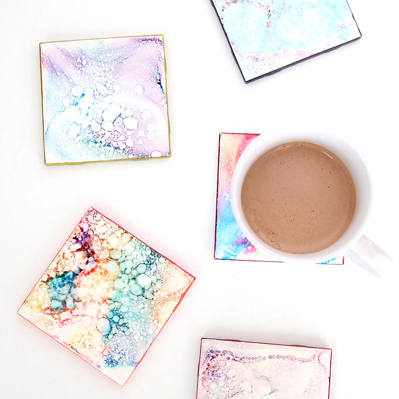 DIY coasters made from white tiles decorated with marbled inks; cup of cocoa on a coaster