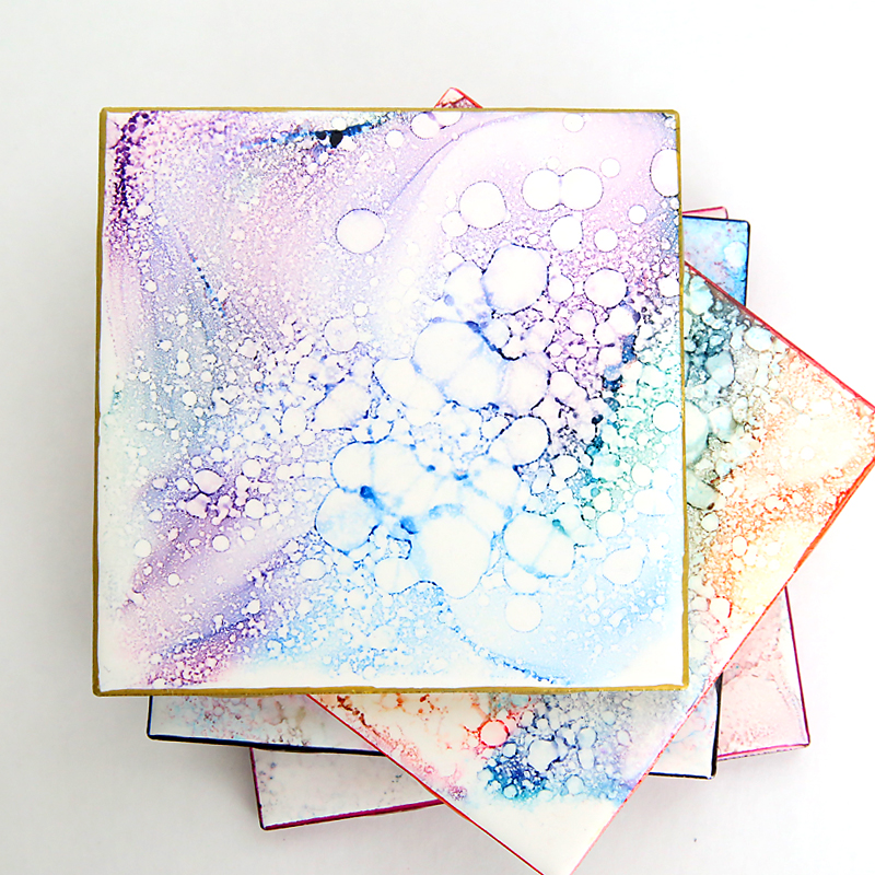 Tiles decorated with alcohol ink to look like granite coasters