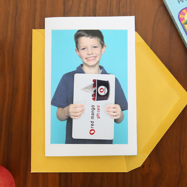a photo of a boy holding a gift card