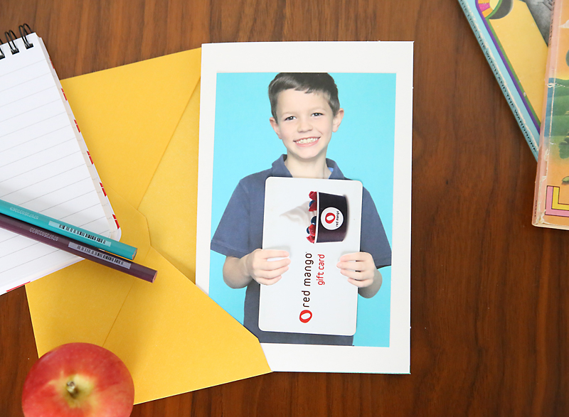 Photo of a boy holding a gift card