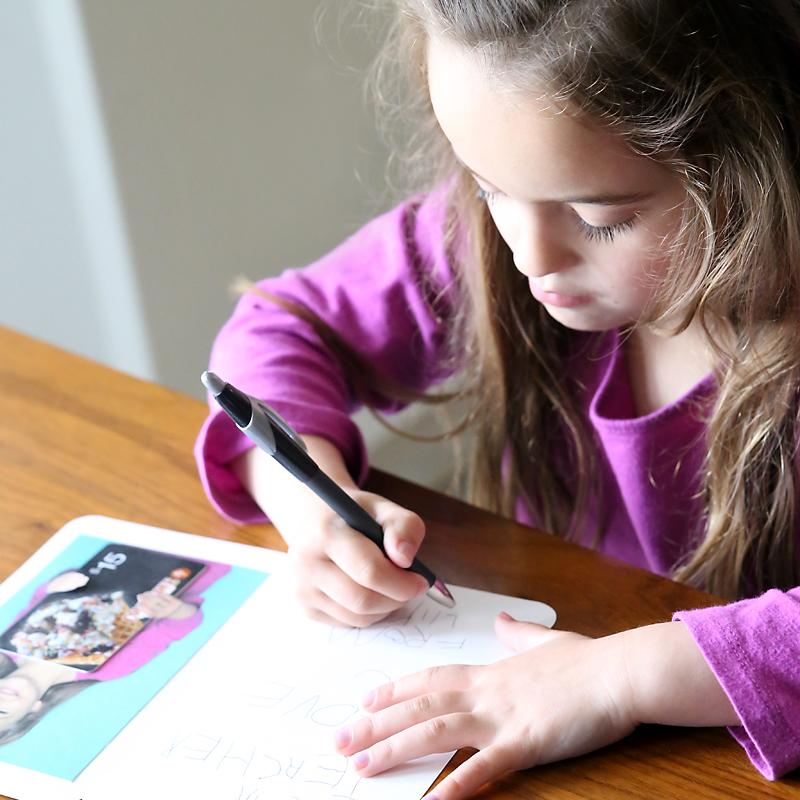 Girl writing a teacher appreciation card