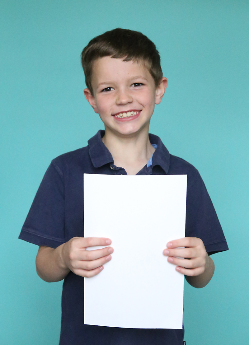 A boy holding a white sheet of paper