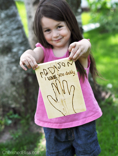 Girl holding a wood burned Father\'s Day card
