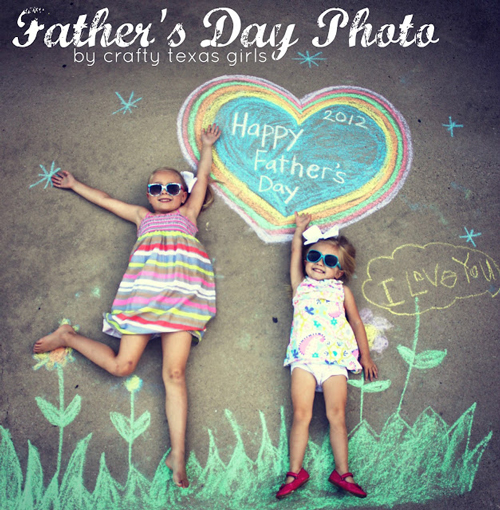 Little girls laying on the sidewalk with Father\'s Day chalk art