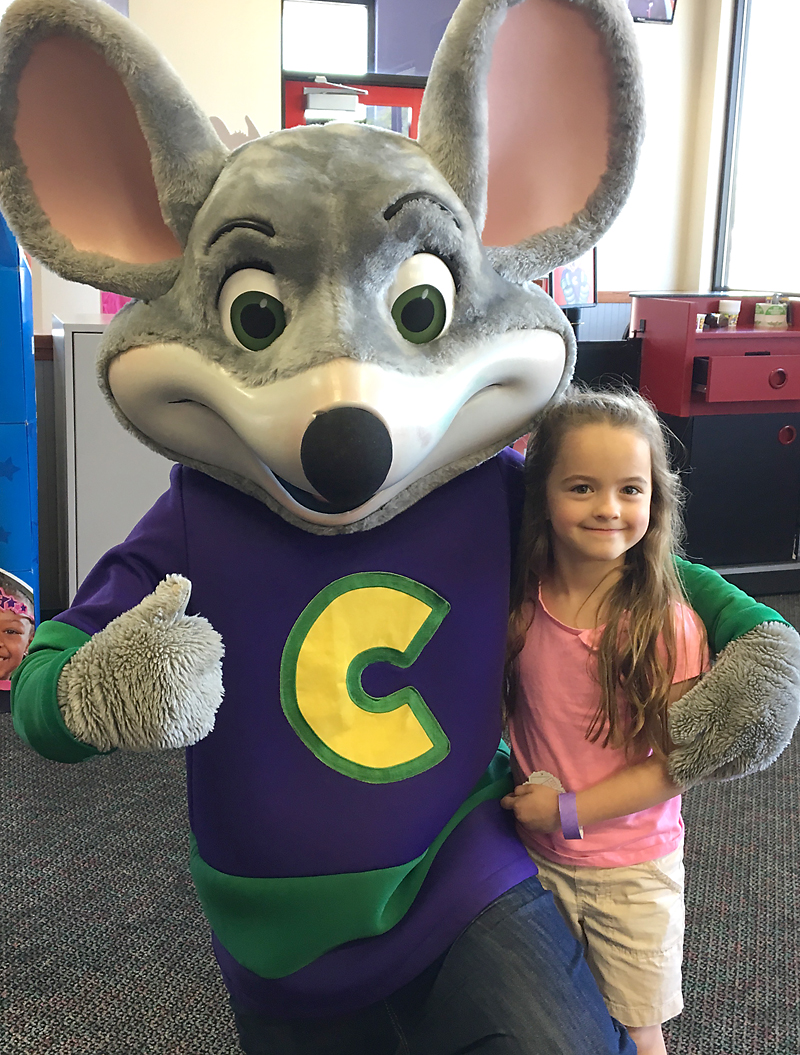 A little girl standing standing next to chuck e cheese mouse