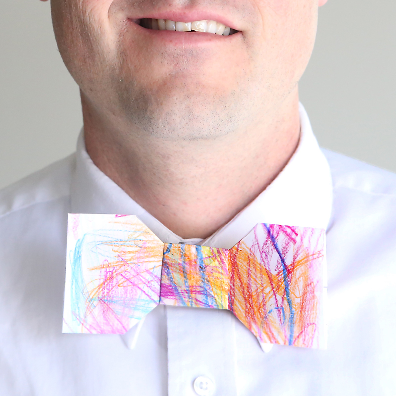 A man wearing a paper orgami bowtie that\'s been colored