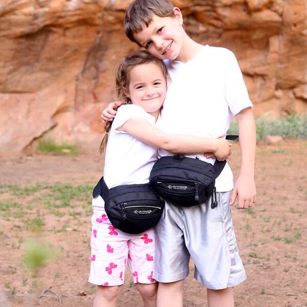 A girl and boy wearing fanny packs hugging each other