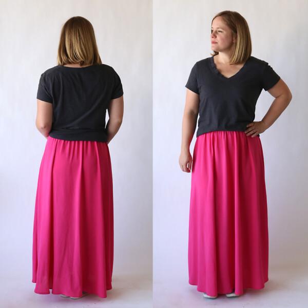A woman wearing a long pink maxi skirt and dark grey t-shirt
