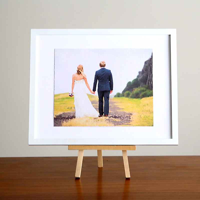 A framed painting of a bride and groom