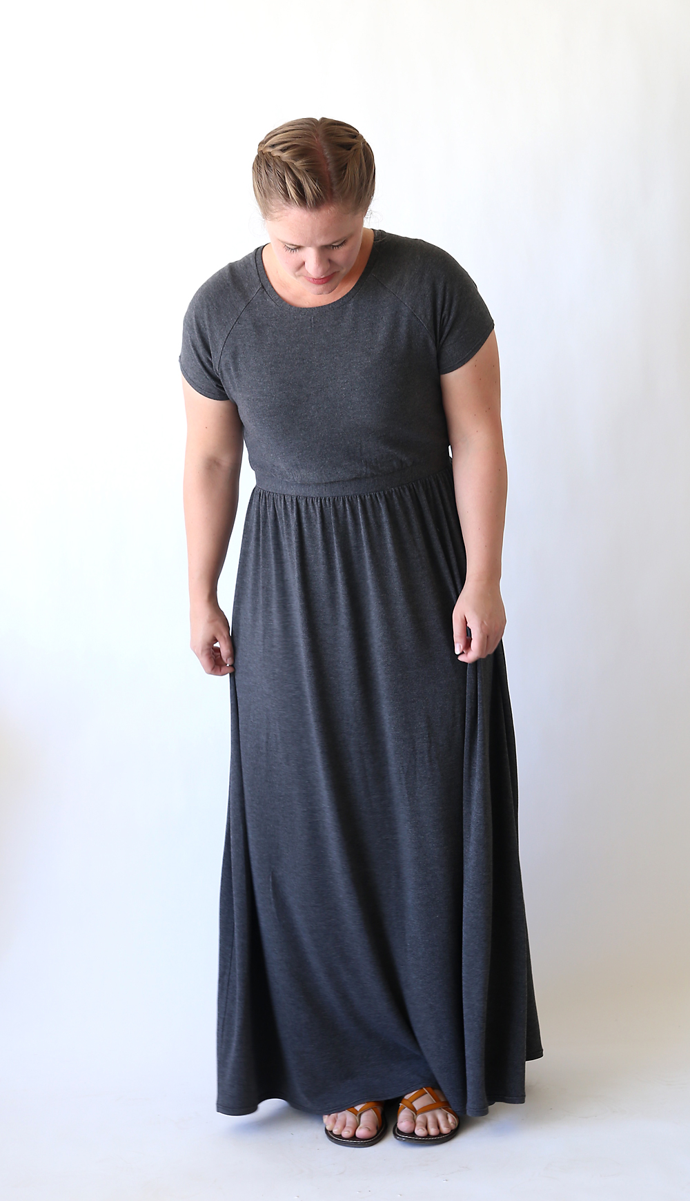 Woman wearing a long grey dress with gathered skirt