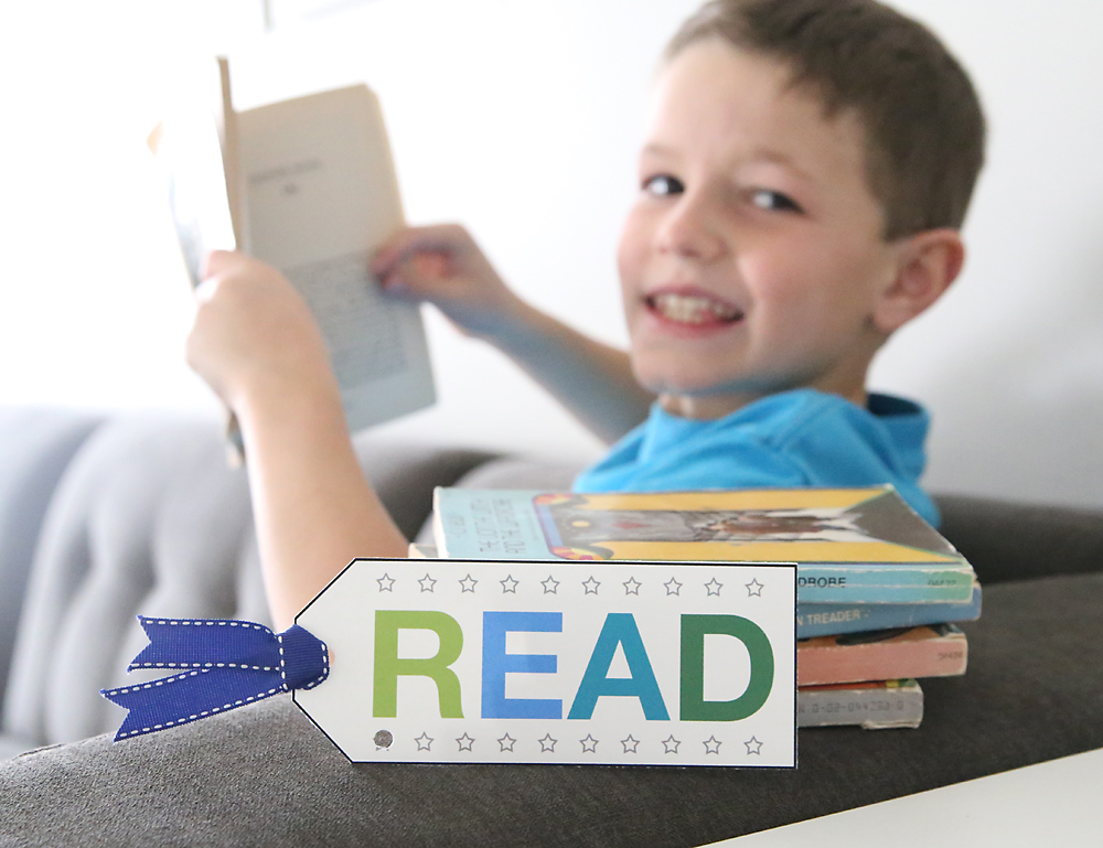 Boy reading a book with a punch card bookmark