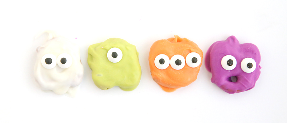Pretzels dipped in white, green, orange, and purple candy melts with candy eyes to look like ghosts and monsters