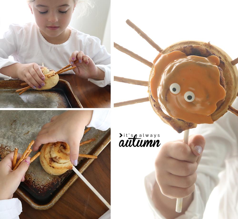 A little girl holding a spider cinnamon roll she has made