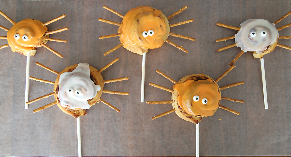 A cinnamon roll on a stick decorated with eyes and pretzel stick legs to look like a spider with orange frosting
