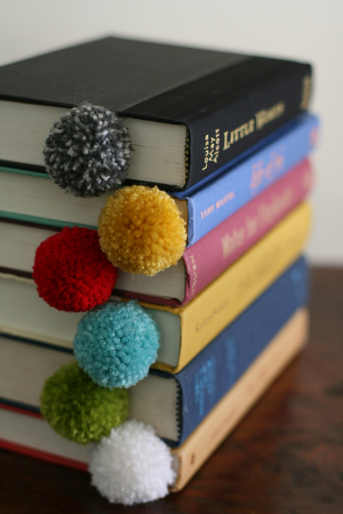 Stack of books with homemade pom pom bookmarks in them