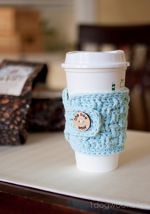 A cup of coffee on a table with a crocheted cozy around it
