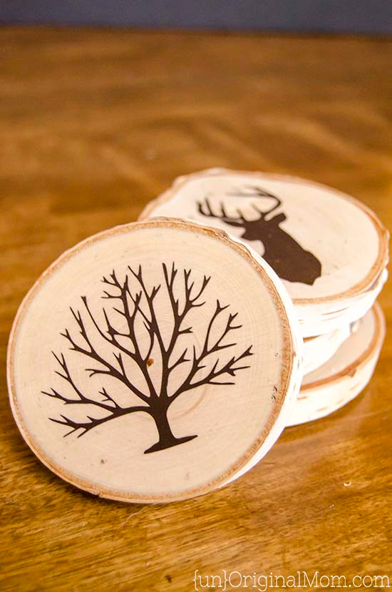DIY coasters made from wood slices decorated with tree shape and antler shape